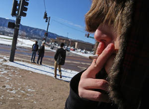 Photo - A high school student, who preferred not to be identified, smokes a cigarette in a de facto smoking area just off the property of Lewis-Palmer High School, in Monument, Colo., Thursday Feb. 20, 2014. A proposal to raise the tobacco age to 21 in Colorado is up for its first review in the state Legislature. The bipartisan bill would make Colorado the first with a statewide 21-to-smoke law. (AP Photo/Brennan Linsley)