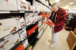 Photo - Richard Randal shops for Valentine's Day chocolates for his wife Wednesday at Russell Stover in Oklahoma City. Photos by Steve Gooch, The Oklahoman