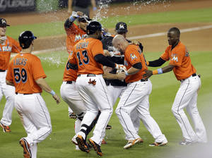 Photo - Miami Marlins' Casey McGehee, second from right, is mobbed by teammates after driving in the game-winning run on a sacrifice fly against the Pittsburgh Pirates in the 10th inning of a baseball game in Miami, Sunday, June 15, 2014. The Marlins won 3-2. (AP Photo/Alan Diaz)