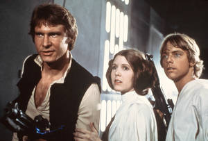 "Photo - FILE - This 1977 file image provided by 20th Century-Fox Film Corporation ahows, from left, Harrison Ford, Carrie Fisher, and Mark Hamill in a scene from ""Star Wars"" movie released by 20th Century-Fox in 1977. Having recently purchased the ""Star Wars"" franchise from Lucasfilm for $4 billion, the Walt Disney Co. is shifting the films into hyperdrive. Not only has Disney already begun working on a new trilogy, to start with J.J. Abrams directing episode seven, but reports this week have said possible spinoffs are being developed for young Han Solo, the bounty hunter Boba Fett and Yoda.  (AP Photo/20th Century-Fox Film Corporation)"