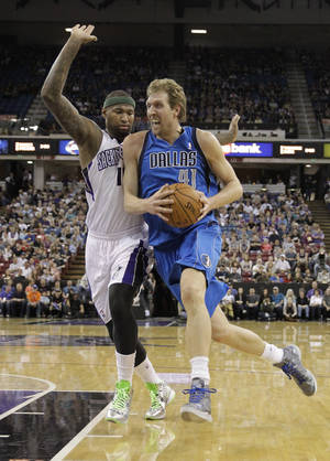 Photo - Dallas Mavericks forward Dirk Nowitzki, of Germany, drives to the basket against Sacramento Kings center DeMarcus Cousins, left, during the first quarter of an NBA basketball game, Sunday, April 6, 2014, in Sacramento, Calif.(AP Photo/Rich Pedroncelli)