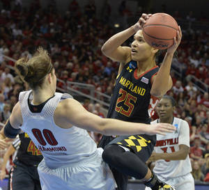 Photo - Maryland's Alyssa Thomas, right, charges into Louisville's Sara Hammond  during the first half of a regional final in the NCAA women's college basketball tournament, Tuesday, April 1, 2014, in Louisville, Ky. (AP Photo/Timothy D. Easley)