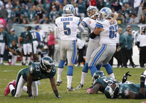 Photo -   Detroit Lions kicker Jason Hanson, center, is congratulated by Dylan Gandy (65) and Nick Harris (5) after kicking a 45-yard field goal to give the Lions a 26-23 overtime victory over the Philadelphia Eagles in an NFL football game, Sunday, Oct. 14, 2012, in Philadelphia. (AP Photo/Mel Evans)