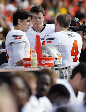 photo - Oklahoma State&#039;s Clint Chelf (10), left, talks with Wes Lunt (11) and J.W. Walsh (4) during a college football game between the Oklahoma State University Cowboys (OSU) and the Baylor University Bears at Floyd Casey Stadium in Waco, Texas, Saturday, Dec. 1, 2012. Photo by Nate Billings, The Oklahoman