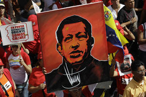 Photo - A supporter of Venezuela's President Hugo Chavez holds up a painting of him during a symbolic inauguration rally for Chavez outside Miraflores presidential palace in Caracas, Venezuela, Thursday, Jan. 10, 2013.  The government organized the unusual show of support for the cancer-stricken leader on the streets on what was supposed to be his inauguration day. Vice President Nicolas Maduro said that even though it wasn't an official swearing-in, Thursday's event still marks the start of a new term for the president following his re-election in October. (AP Photo/Fernando Llano)