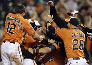 Photo - Baltimore Orioles' David Lough, in batting helmet, celebrates with teammates after hitting a game-winning single in the 12th inning of a baseball game against the Toronto Blue Jays, Saturday, April 12, 2014, in Baltimore. Stephen Lombardozzi scored on the play, and Baltimore won 2-1. (AP Photo/Patrick Semansky)