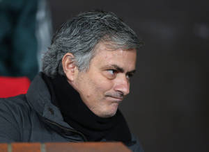 photo - Real Madrid's coach Jose Mourinho from Portugal grimaces as he takes his seat ahead of the Champions League round of 16 soccer match against Manchester United at Old Trafford Stadium, Manchester, England, Tuesday, March 5, 2013. (AP Photo/Jon Super)