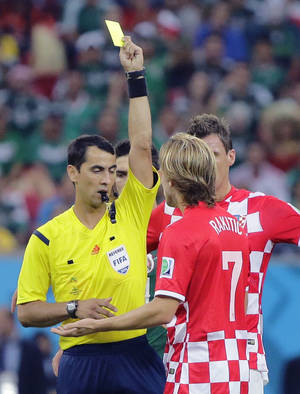 Photo - Referee Ravshan Irmatov of Uzbekistan gives a yellow card to Croatia's Ivan Rakitic during the group A World Cup soccer match between Croatia and Mexico at the Arena Pernambuco in Recife, Brazil, Monday, June 23, 2014. (AP Photo/Sergei Grits)