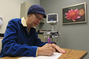 Photo - Kathleen Sanford performs neurological cognitive tests during an appointment Monday, Dec. 17, 2012, in Columbus, Ohio. Sanford is an Alzheimer's patient that has a deep brain stimulation implant as part of a study at Ohio State University. In small experiments, scientists are implanting pacemaker-like devices deep in the brains of some people with early-stage Alzheimer's in hopes of slowing the disease's damage. The tiny wires send mild jolts of electricity to stimulate the brain.  (AP Photo/Jay LaPrete)
