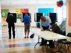 Photo - Rudy Garcia, helps his grandfather Processo Chavez, 82,  read the ballot at precinct 75 on Tuesday, June 3, 2014 in Santa Fe, N.M.  Voting traffic at the polls for the New Mexico primary was reportedly slow Tuesday as officials prepared for a low turnout. (AP Photo/The Santa Fe New Mexican, Luis Sanches Saturno)