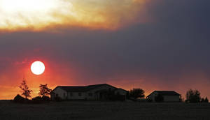 Photo - The sun sets through wildfire smoke Sunday, June 23, 2013, near Monte Vista, Colo.  A large wildfire near a popular summer retreat in southern Colorado continues to be driven by winds and fueled by dead trees in a drought-stricken area, authorities said. (AP Photo/Gregory Bull)