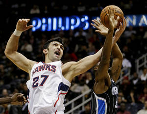 Photo -   Atlanta Hawks' Zaza Pachulia (27), of the Republic of Georgia, grabs a rebound from Orlando Magic's E'Twaun Moore in the second quarter of an NBA basketball game, Monday, Nov. 19, 2012, in Atlanta. (AP Photo/David Goldman)