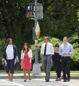 Photo - President Barack Obama crosses the street as he walks to have lunch at a Chipotle Mexican Grill in Washington, Monday, June 23, 2014, prior to attending the White House Summit on Working Families. Walking with Obama, from left are, Shirley Young, Lisa Rumain, Shelby Ramirez,  and Rodger Trombley. Obama is encouraging more employers to adopt family-friendly policies, part of a broader effort to convince employers that providing more flexibility is good for business as well as workers. (AP Photo/Pablo Martinez Monsivais)