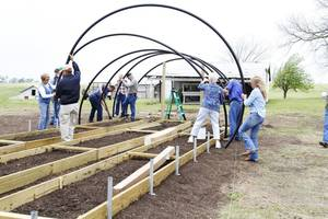 Photo - Participants at a previous workshop use tubing to construct a hoop house frame.  Photo provided