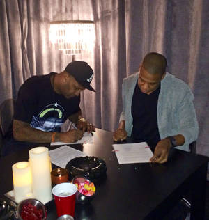 Photo - In this photo provided by Roc Nation Sports, New York Yankees pitcher CC Sabathia, left, signs papers with Jay-Z as Sabathia signs on with Jay-Z's sports agency, Roc Nation Sports, Thursday, Jan. 16, 2014, in New York. Sabathia will join former teammate Robinson Cano in Roc Nation Sport's emerging client base. (AP Photo/Roc Nation Sports)
