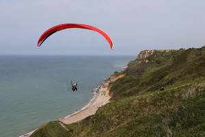 Photo - This April 24, 2014 photo shows people paragliding over the D-Day beaches, in Port en Bessin, western France. Local officials estimate that several hundred thousand tourists will flock to Normandy this summer, attracted by the 70th anniversary of D-Day. (AP Photo/David Vincent)