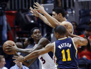 Photo - Atlanta Hawks shooting guard Louis Williams (3) is challenged by Utah Jazz power forward Derrick Favors, top, and point guard Earl Watson (11) during the first half of an NBA basketball game on Friday, Jan. 11, 2013, in Atlanta.  (AP Photo/John Bazemore)