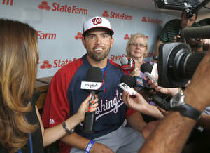 Photo - Washington Nationals' David DeJesus, center, talks with reporters after he was traded by the Chicago Cubs to the National before a baseball game between the Cubs and Nationals at Wrigley Field, Monday, Aug. 19, 2013, in Chicago. (AP Photo/Charles Rex Arbogast)