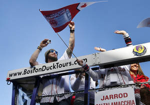 Photo - Boston Red Sox catcher Jarrod Saltalamacchia takes pictures as he rides in a duck boat during a rolling rally in Boston, Saturday, Nov. 2, 2013 to celebrate their World Series championship. (AP Photo/Elise Amendola)