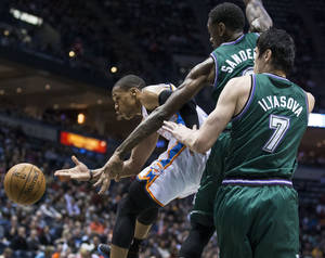 Photo - Oklahoma City Thunder's Russell Westbrook, left, passes the ball as Milwaukee Bucks' Larry Sanders and Ersan Ilyasova defend during the first half of an NBA basketball game on Saturday, March 30, 2013, in Milwaukee. (AP Photo/Tom Lynn)  ORG XMIT: WITL104
