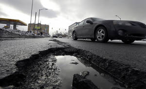 Photo - FILE - This Feb. 11, 2014 file photo shows a car driving by a pothole in Detroit, as a fuel station is seen in the background. Congress has kept federal highway and transit programs limping along for the past six years, unable to decide how best to pay for them. Lawmakers' indecision mirrors what The Associated Press and GfK found in a recent opinion survey. (AP Photo/Carlos Osorio, File)