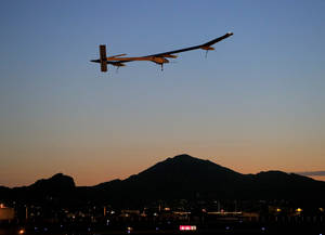 Photo - Solar Impulse, piloted by André Borschberg, takes flight during the second leg of the 2013 Across America mission, at dawn, Wednesday, May 22, 2013, from Sky Harbor International Airport in Phoenix. The solar powered aircraft is scheduled to land at Dallas/Fort Worth International Airport on Thursday May 23. The plane's creators, Bertrand Piccard and Borschberg, said the trip is the first attempt by a solar airplane capable of flying day and night without fuel to fly across America. (AP Photo/Matt York)