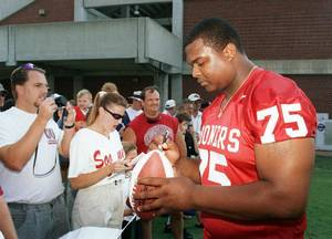 photo - Sammy Williams signs a football after OU picture day was opened to the fans.