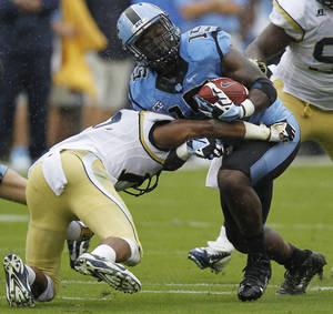 Photo - Georgia Tech defensive back Demond Smith (12) hits North Carolina running back A.J. Blue (15) during the first half of an NCAA football game, Saturday, Sept. 21, 2013, in Atlanta. (AP Photo/Mike Stewart)