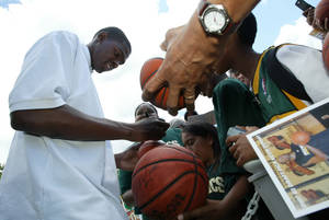 "Photo - Kevin Durant, shown here signing autographs shortly after he was drafted by the then-Seattle SuperSonics, still goes out of his way to accommodate fans. ""They make time for us,"" Durant said. ""So that's the least I can do, just showing them that I appreciate them."" AP PHOTO"