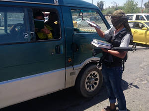 Photo - A fighter with the al-Qaida-inspired Islamic State of Iraq and the Levant (ISIL) distributes a copy of the Quran, Islam's holy book, to a driver in central northern city of Mosul, 225 miles (360 kilometers) northwest of Baghdad, Iraq, Sunday, June 22, 2014. Sunni militants on Sunday captured two border crossings, one along the frontier with Jordan and the other with Syria, security and military officials said, as they pressed on with their offensive in one of Iraq's most restive regions. (AP Photo)
