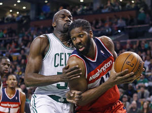 Photo - Washington Wizards forward Nene Hilario, right, drives against Boston Celtics center Joel Anthony during the first quarter of an NBA basketball game in Boston, Wednesday, April 16, 2014. (AP Photo/Elise Amendola)
