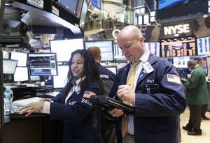 Photo - Traders work Tuesday on the floor of the New York Stock Exchange in New York. The U.S. stock market extended its longest and deepest slump of the year Tuesday, caught between a recurring nightmare of European debt and the beginning of uncertain corporate earnings reports at home. AP Photo