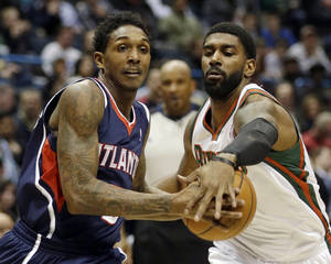 Photo - Atlanta Hawks' Louis Williams, left, drives against Milwaukee Bucks' O.J. Mayo during the first half of an NBA basketball game Saturday, Jan. 25, 2014, in Milwaukee. (AP Photo/Jeffrey Phelps)