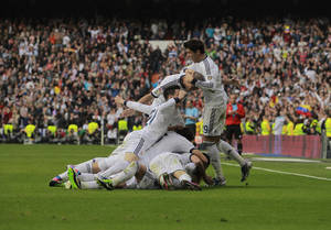 photo - Real Madrid's Sergio Ramos, unseen, celebrates his goal with team mates during a Spanish La Liga soccer match against FC Barcelona at the Santiago Bernabeu stadium in Madrid, Spain, Saturday, March 2, 2013. (AP Photo/Andres Kudacki)
