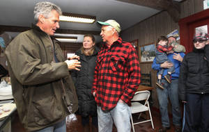 Photo - This photo taken March 22, 2014 shows former Massachusetts Sen. Scott Brown, left, talking with Peter Thompson at his maple sugar house in Orford, N.H. Brown is fighting to re-write political history as he tours New Hampshire. But there are early signs that the state's notoriously feisty voters may be reluctant to embrace the recent Republican transplant. Brown joined New Hampshire's U.S. Senate race roughly a week ago. He moved to the state 13 weeks ago. Brown is trying to become the third person to serve more than one state in the Senate. The last one was elected more than two centuries ago. His residency figures to play prominently in his quest to defeat Democratic Sen. Jeanne Shaheen this fall.  (AP Photo/Jim Cole)