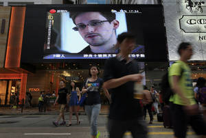 Photo - FILE - This June 23, 2013 file photo shows a TV screen shows a news report of Edward Snowden, a former CIA employee who leaked top-secret documents about sweeping U.S. surveillance programs, at a shopping mall in Hong Kong. The saga of Edward Snowden and the NSA makes one thing clear: The United States' central role in developing the Internet and hosting its most powerful players has made it the global leader in the surveillance game . Other countries, from dictatorships to democracies, are also avid snoopers, tapping into the high-capacity fiber optic cables to intercept Internet traffic, scooping their citizens' data off domestic servers, and even launching cyberattacks to win access to foreign networks. (AP Photo/Vincent Yu, File)
