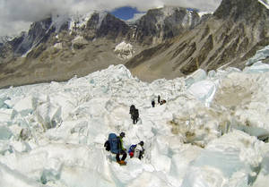 Photo - FILE - In this May 22 2013 file photo, climbers descend Khumbu Icefall on their way back to Base Camo after summitting the 8,850-meter (29,035-foot) Mount Everest. With its dreams of covering a daredevil's attempt to jump off Mount Everest over, the Discovery network is instead making a documentary on the avalanche, Friday, 18, 2014, that killed more than a dozen mountain guides. Discovery President Eileen O'Neill said Tuesday, April 22,  the network hopes to air the film within the next few weeks. Discovery will encourage viewers to donate to a relief fund for families of the Sherpa guides killed in the disaster. Several of the Sherpas killed were helping prepare for American Joby Ogwyn's planned jump from the summit in a wingsuit. Discovery planned to show the stunt on live television May 11.(AP Photo/ Pasang Geljen Sherpa, FIle)