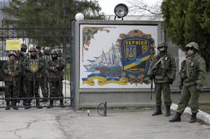 Photo - Ukrainian soldiers, left and unidentified gunmen, right, guard the gate of  an infantry base in Privolnoye, Ukraine, Sunday, March 2, 2014. Hundreds of unidentified gunmen arrived outside Ukraine's infantry base in Privolnoye in its Crimea region. The convoy includes at least 13 troop vehicles each containing 30 soldiers and four armored vehicles with mounted machine guns. The vehicles — which have Russian license plates — have surrounded the base and are blocking Ukrainian soldiers from entering or leaving it. (AP Photo/Darko Vojinovic)