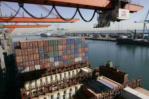Photo - FILE - In this Dec. 4, 2006 file photo, shows are unloaded from the APL Singapore vessel at the port of Los Angeles. The West Coast ports that are America's gateway for hundreds of billions of dollars of trade with Asia and beyond are no stranger to labor unrest and even violence. Now, the contract that covers nearly 20,000 dockworkers is set to expire, and businesses that trade in everything from apples to iPhones are worried about disruptions _ as the summer cargo crush begins. (AP Photo/Damian Dovarganes,file)