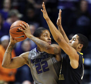 Photo - Kansas State guard Rodney McGruder (22) is covered by West Virginia guard Gary Browne (14) during the first half of an NCAA college basketball game in Manhattan, Kan., Monday, Feb. 18, 2013. (AP Photo/Orlin Wagner)