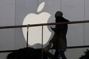 Photo - FILE - In this Dec. 23, 2013 file photo, a woman using a phone walks past Apple's logo near its retail outlet in Beijing. Apple reports quarterly earnings on Wednesday, April 23, 2014. (AP Photo/Ng Han Guan, File)
