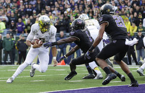 Photo - Oregon quarterback Marcus Mariota, left, runs the ball on a keeper play against Washington in the first half of an NCAA college football game, Saturday, Oct. 12, 2013, in Seattle. Mariota was stopped short of the goal line, but Oregon scored a touchdown on the next play. (AP Photo/Ted S. Warren)