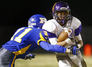 Photo - Anadarko's Brayden Alexander tries to get past Piedmont's Colby Bricker during their high school football game in Piedmont, Okla., Friday, October 25, 2013. Photo by Bryan Terry, The Oklahoman