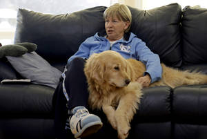 Photo - In this Wednesday, Dec. 18, 2013, photo, North Carolina women's basketball coach Sylvia Hatchell relaxes at home with her dog Maddie in Chapel Hill, N.C. After being diagnosed with leukemia, Hatchell has temporarily stepped away from her coaching duties to focus on her treatment. (AP Photo/Gerry Broome)
