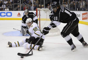 photo - Dallas Stars right wing Jaromir Jagr, center, of the Czech Republic, battles for the puck with Los Angeles Kings center Anze Kopitar, right, of Slovenia, as goalie Jonathan Quick looks on during the third period of their NHL hockey game, Thursday, March 21, 2013, in Los Angeles. The Stars won 2-0.  (AP Photo/Mark J. Terrill)
