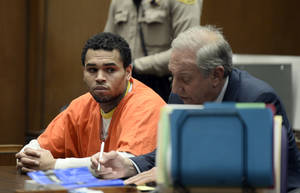 Photo - Chris Brown, left is shown in court with his attorney, Mark Geragos Friday May 9, 2014 in Los Angeles. Brown on Friday admitted a probation violation over an altercation last year outside a hotel in Washington, D.C., and was sentenced to remain on probation and serve an additional 131 days in jail. (AP Photo/Paul Buck, POOL)