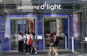 Photo - Visitors enter a showroom of Samsung Electronics' at its headquarters in Seoul, South Korea, Friday, July 26, 2013. Samsung Electronics reported a record-high profit for a sixth straight quarter but still disappointed investors who had higher expectations for the world's largest smartphone maker. (AP Photo/Lee Jin-man)