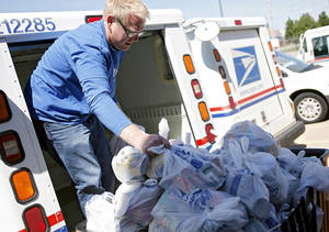 photo - Michael Higginbottom unloads food from a mail truck as he helps volunteers sort food during the Stamp Out Hunger food drive at the Britton Post Office in northwest Oklahoma City on May 14, 2010. Every year, letter carriers collect nonperishable food donations from households on their route to benefit the Regional Food Bank of Oklahoma. OKLAHOMAN  ARCHIVE PHOTO