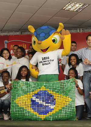 photo -   In this photo released by Coca-Cola Brasil, youths pose for photos with the mascot of the 2014 World Cup soccer tournament as they hold up a Brazilian flag made out of bottle caps at the Morro dos Macacos favela in Rio de Janeiro, Brazil, Monday, Sept. 17, 2012. The mascot of the 2014 World Cup is a yet to-be-named Brazilian endangered armadillo. FIFA said Brazilians will have until mid-November to choose the mascot&#039;s name from three choices: Amijubi, Fuleco and Zuzeco. (AP Photo/Coca-Cola Brasil, Ismar Ingber)  