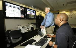 Photo - Michael Murphy, standing, director of the Metropolitan Medical Response System, and Michael Curtis, seated, coordinator of the Oklahoma City Medical Emergency Response Center, examine a weather screen at the response center April 23, 2009. <strong>Paul B. Southerland - The Oklahoman</strong>